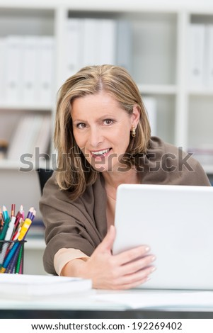 Attentive attractive businesswoman peering around the side of her laptop computer at the camera as she sits at her desk in the office