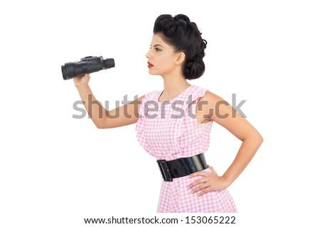 Attentive black hair model using binoculars on white background - stock photo