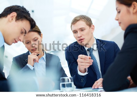 Attentive business partners listening to new ideas and thinking them over at meeting - stock photo