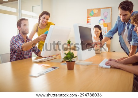 Attentive business team working on laptops in a bright office - stock photo
