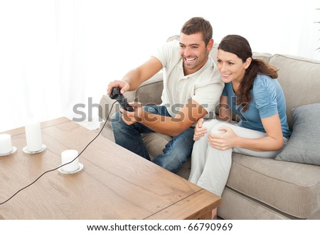Attentive couple playing video game together in the living room at home - stock photo