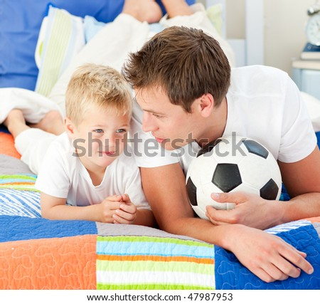 Attentive father and his son playing with a soccer ball lying on bed - stock photo