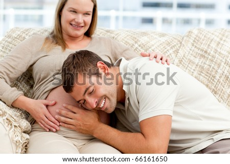 Attentive future dad listening to the belly of his wife sitting on the sofa in the living room - stock photo