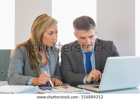 Attentive mature businessman showing something on computer to an attentive blonde businesswoman at office - stock photo