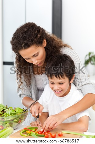 Attentive mother helping her son to cut vegetables in the kitchen - stock photo