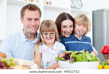 Attentive parents and their children cooking together in the kitchen