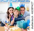 Attentive parents celebrating their son's birthday in the kitchen - stock photo