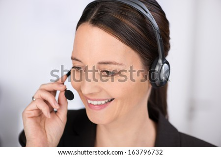Attentive receptionist talking on a headset smiling as she listens to the customer or client speaking - stock photo