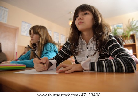 Attentive schoolgirl is listening to her teacher during lesson - stock photo