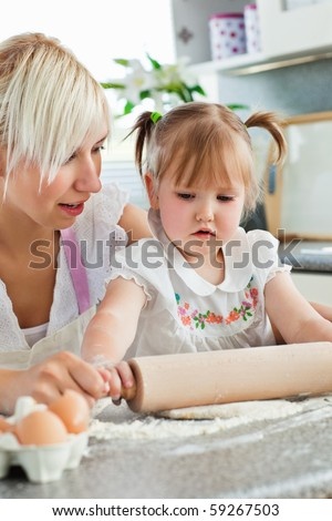 Attentive young mother baking with her daughter in the kitchen - stock photo