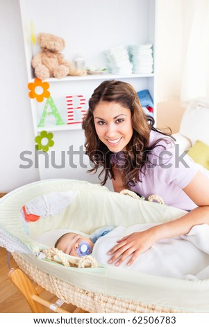 Attentive young mother taking care of her adorable baby at home - stock photo