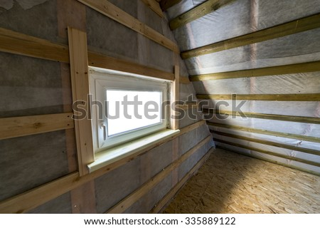 Attic with vapor barrier and window - stock photo