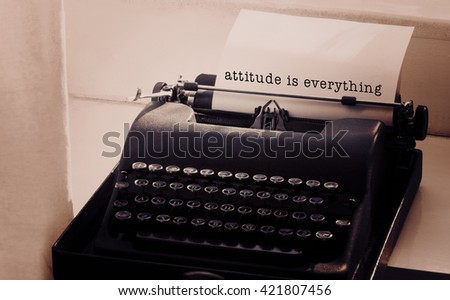 Attitude is everything message on a white background against typewriter on a table - stock photo