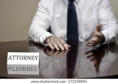 Attorney at Law sitting at desk holding pen with files with business card - stock photo