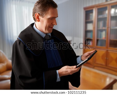 Attorney wearing classic gown with tablet in his office