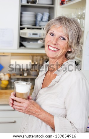 Attracive modern elderly woman enjoying a cup of cappuccino in her kitchen smiling in appreciation - stock photo