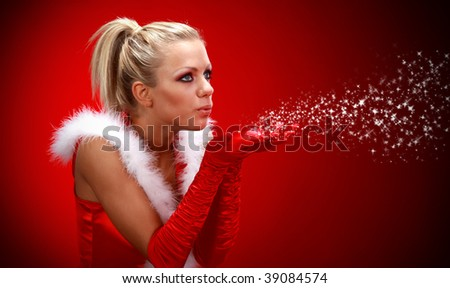 Attracive sexy girl in santa cloth blowing snow from hands. - stock photo