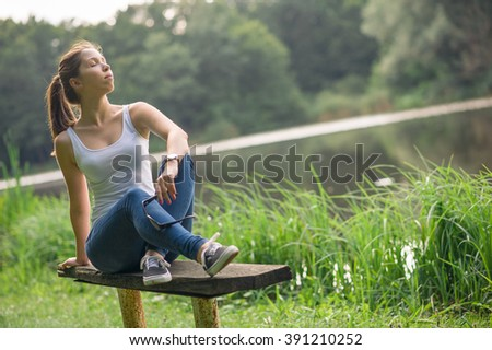Attractice young caucasian brown haired girl in white tank sitting and relaxing on wooden bench on peaceful the sunny summer lakeside - stock photo