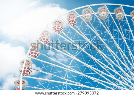 Attraction Ferris wheel against the blue sky with a few clouds on a sunny day toned photo - stock photo