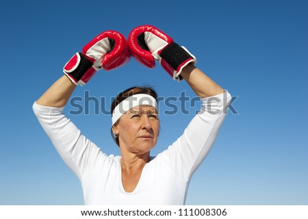 Attractive active senior woman exercising with boxing gloves, posing confident and focused, isolated with blue sky as background and copy space. - stock photo