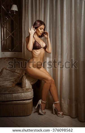 Attractive adult brunette girl in beautiful lingerie on the chair. Sexual woman in bra. Seduction woman in  bra. Hot woman in bra. - stock photo