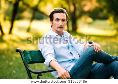 attractive adult man sitting alone on bench in park