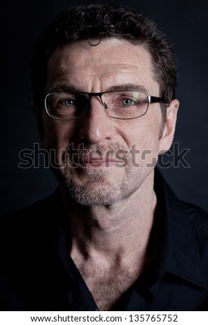 attractive adult man with glasses and black shirt on black background