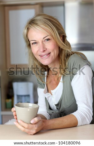 Attractive adult woman holding mug in home kitchen - stock photo