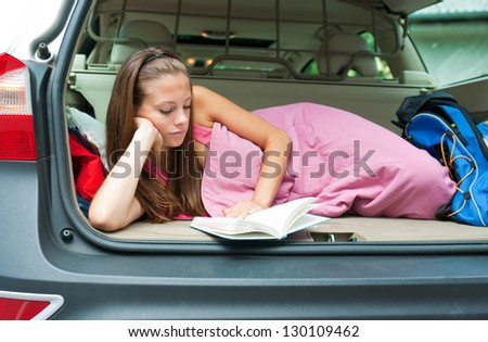 attractive adult woman reading book in trunk of her car - stock photo