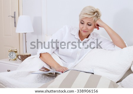 Attractive adult woman relaxing in bed, reading newspaper. Home interior. - stock photo