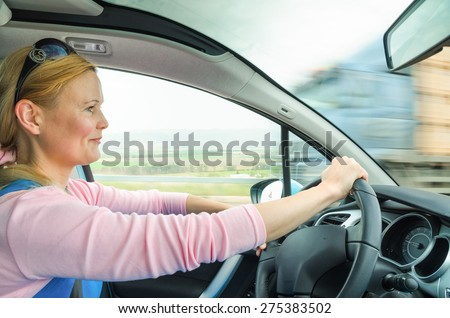 Attractive adult woman safe and carefully driving car on suburban road. Inside the auto photo with high speed oncoming lorry truck blurred in motion.