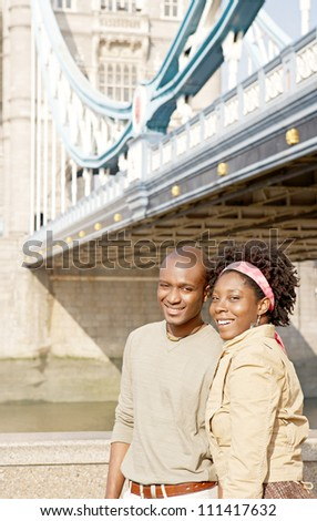 Attractive african american couple walking passed Tower Bridge in London, smiling. - stock photo