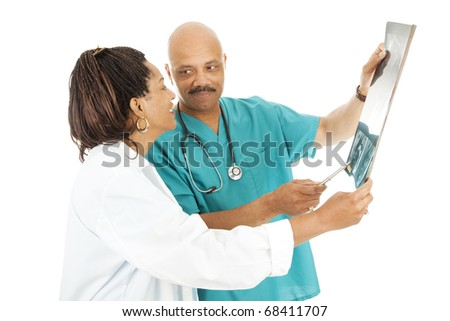Attractive african-american doctors reviewing a patient's x-rays.  Isolated on white. - stock photo