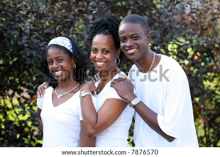 attractive african-american family dressed in white smiling outdoors - stock photo