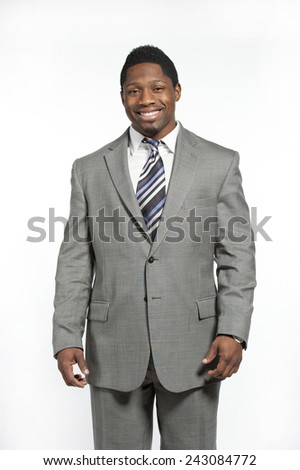 Attractive African American male model wearing a gray suit with a modern tie posing in a studio on a white background while looking at the camera while smiling. - stock photo