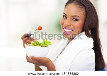 attractive african american woman eating fresh green salad at home - stock photo