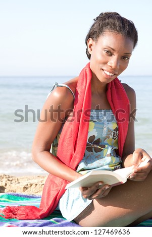 Attractive african-american woman reading a book while sitting on a stripy towel on a golden sand beach while on vacation, smiling. - stock photo