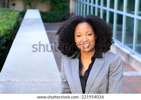 Attractive African AmericanBusiness Professional BusinessWoman with Black Hair Smiling and Happy Wearing a Suit - stock photo