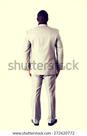 Attractive african businessman standing back - stock photo