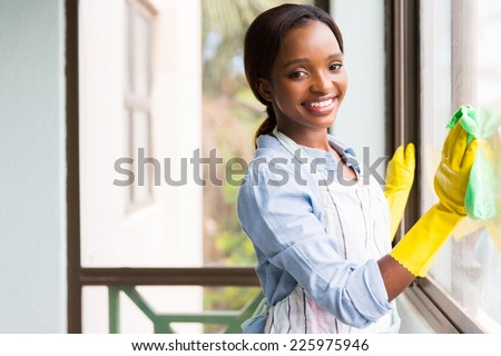 attractive african girl cleaning window glass - stock photo