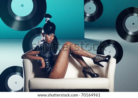 Attractive african woman siting in white chair on vinyl records background - stock photo