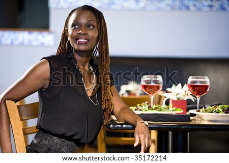 Attractive African woman sitting at a table in restaurant - stock photo