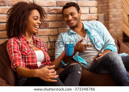 Attractive Afro-American couple using tablet, holding a cup and laughing while sitting on beanbag chairs against brick wall - stock photo