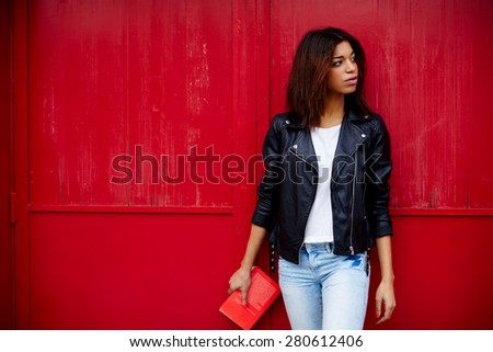 Attractive afro american female posing on red wall background in urban setting, young woman holding book in the hand while strolling in the city at her recreation time,copy space for your text message - stock photo