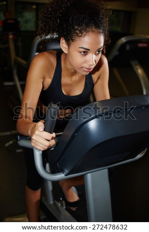 Attractive afro american girl dressed in sport bra riding on spinning bike at fitness center - stock photo