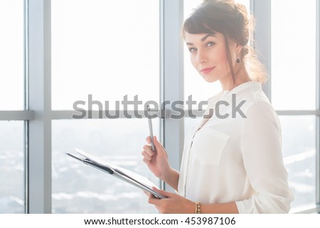 Attractive ambitious businesswoman standing in modern office, holding paper folder, looking at camera, smiling - stock photo