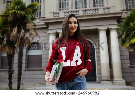 Attractive american student girl standing against university building holding books - stock photo