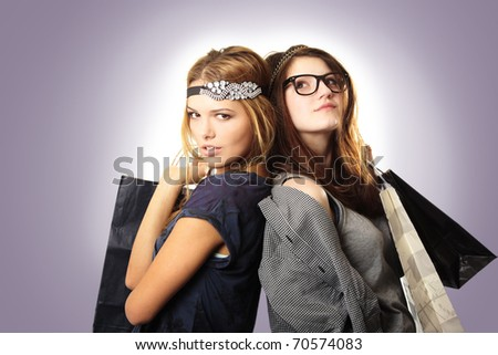 Attractive and cool looking teenage girls with headpieces holding shopping bags on gradient background - stock photo
