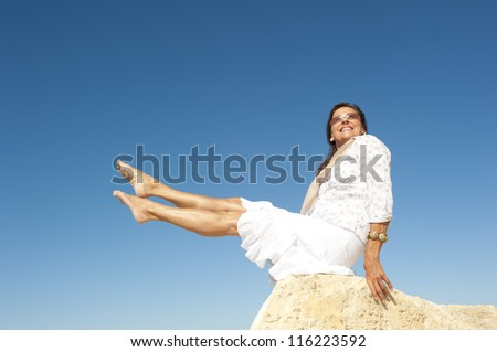 Attractive and fit and healthy looking middle aged woman sitting on rock with legs up in air, isolated with blue sky as background and copy space. - stock photo