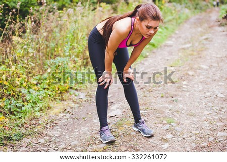 Attractive and fit sportswoman stands exhausted with hands put into knees after hard training on a country road. Running at countryside led to fatigue - stock photo